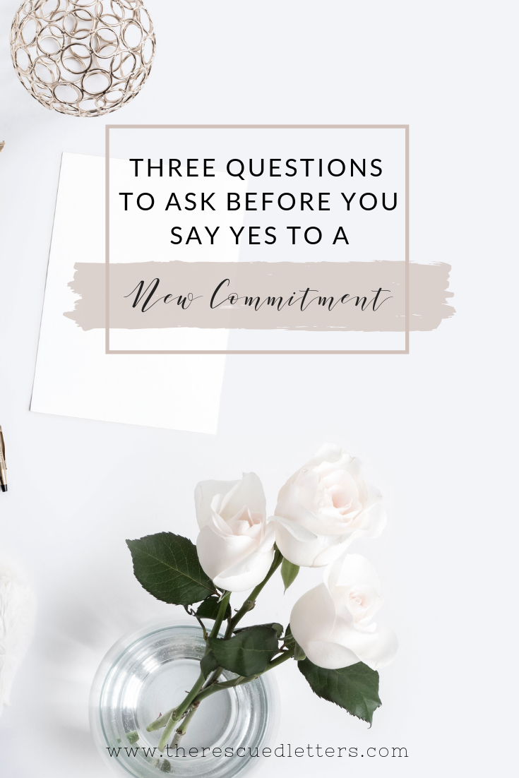 Post title for Three Questions to Ask Before You Say Yes to a New Commitment on a white feminine desktop with roses and stationary