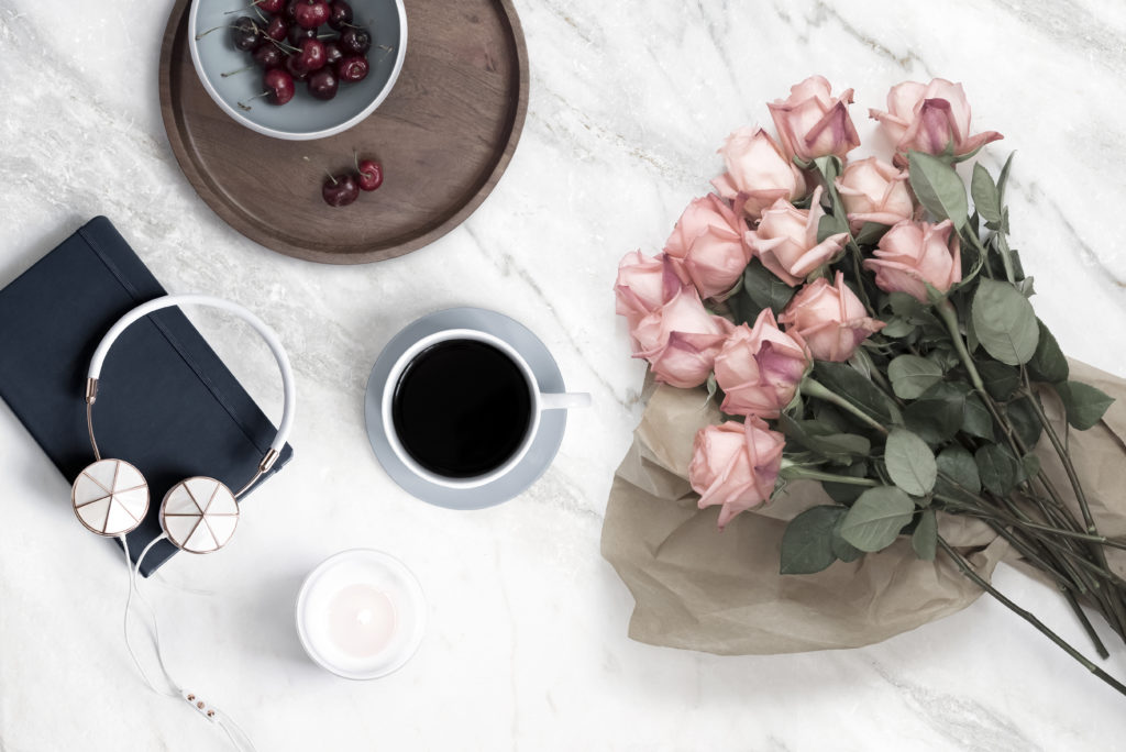 bouquet of pastel pink roses, a bowl of cherries, a cup of coffee, a candle, headphones, and a journal