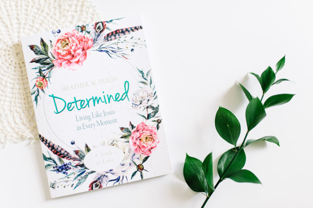 Determined Bible study participant workbook on a table with a doily cloth and branch of greenery