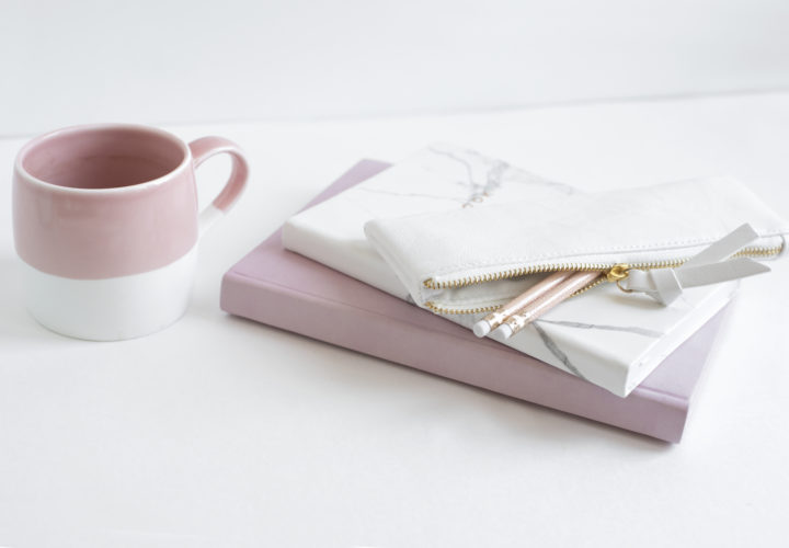 pink mug, pink notebook, and marble journal with pencil case on a marble desktop