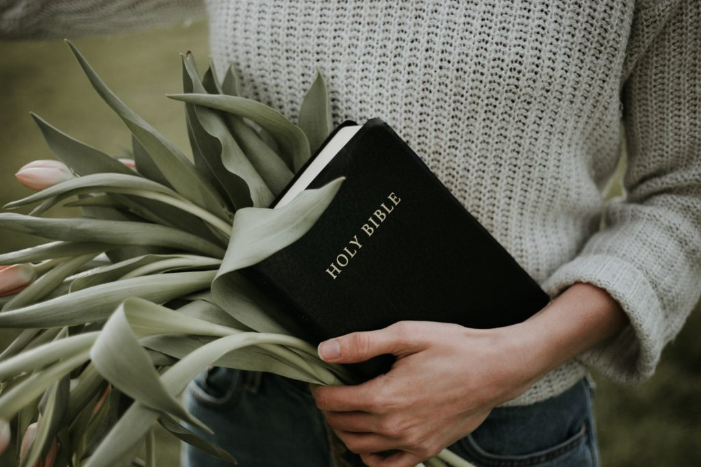 Woman holding the Bible and a bunch of tulips.