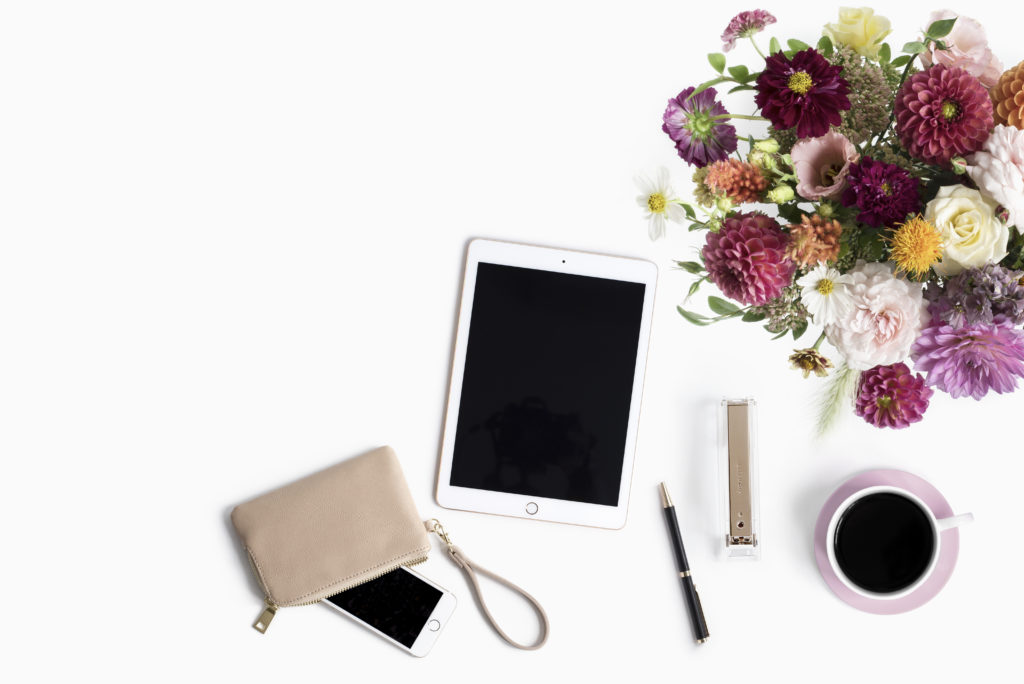Fall flowers, iPad, clutch wallet, miscellaneous desk items, and a cup of coffee on a white background